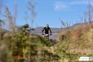 A single participant crests a climb at the National MTB Series