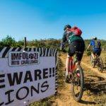 """Riders passing a """"Beware Lions"""" sign on the iMfolozi MTB Challenge route."""