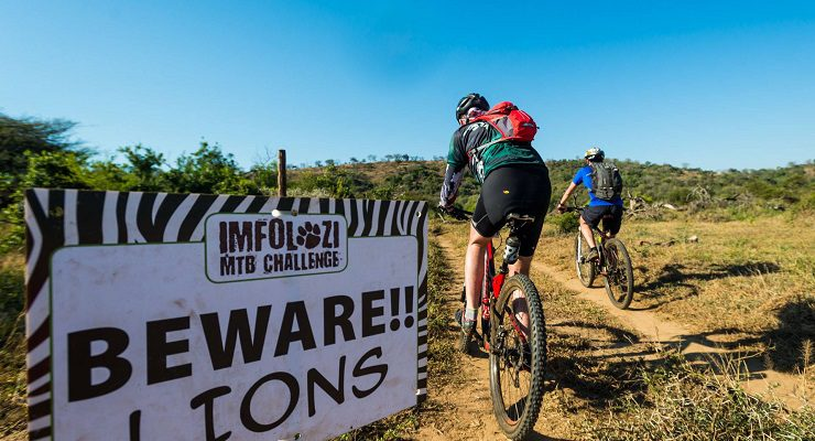 "Riders passing a ""Beware Lions"" sign on the iMfolozi MTB Challenge route."