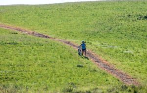 A picture of a rider waving at the photographer during stage one of the Drak Descent.