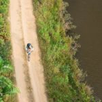 Aerial shot of a solo rider taking on a track alongside a river during the sani2c Race. Photo: Anthony Grote