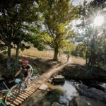 A mountain biker crosses a wooden bridge on day one of sani2c Adventure