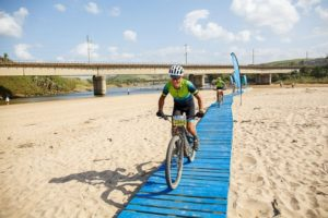 Rider on a bridge over sand on the final day of the sani2c Trail