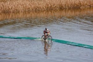 A rider crosses a bridge over water on day one of sani2c Trail.