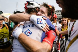 Groupama-FDJ's Arnaud Demare embraces a fellow rider after stage 18 of the Tour de France