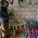Nhlanhla Thabede of the Ladysmith Cycling Academy pictured standing with trophies and bicycles in a garage. Photo: Supplied